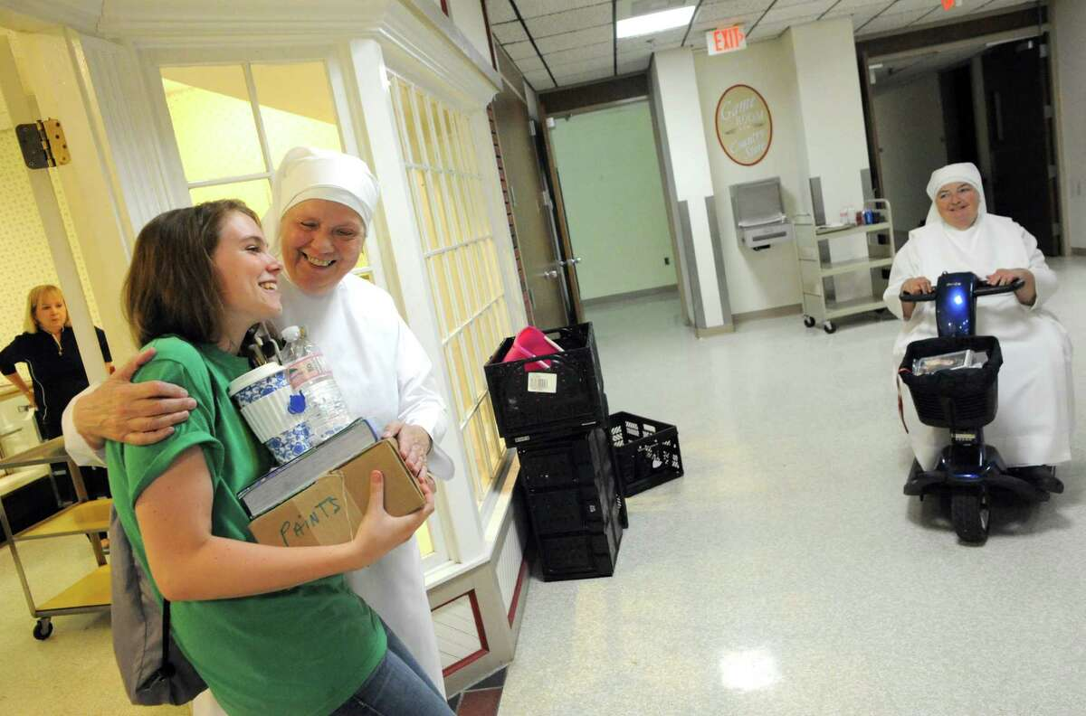 Volunteer Joanie McMahon of Delmar gets a hug from Sister Frances as McMahon helps The Little Sisters of the Poor pack on Thursday Aug.14, 2014 in Latham, N.Y. The Little Sisters of the Poor are leaving the Capital Region after 143 years. (Michael P. Farrell/Times Union)