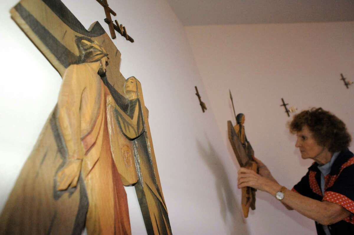 Volunteer Helen Gallagher takes down the Stations of the Cross in The Little Sisters of the Poor chapel on Thursday Aug.14, 2014 in Latham, N.Y. The Little Sisters of the Poor are leaving the Capital Region after 143 years. (Michael P. Farrell/Times Union)
