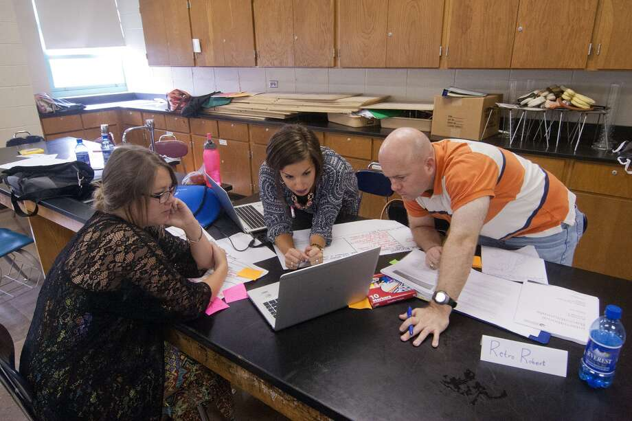 "Teachers Ari Bertulli of Lamar High School, Rachel Settle of Chavez High School and Robert Bickley of Aldine Eisenhower High Scool work on curriculum at a recent International Baccalaureate workshop at Lamar High School, which was the site of the Houston Independent School District's fall IB teachers' conference. Said Lamar Principal James McSwain, ""We're one of the largest IB schools in the country."" Photo: R. Clayton McKee, Freelance / © R. Clayton McKee"