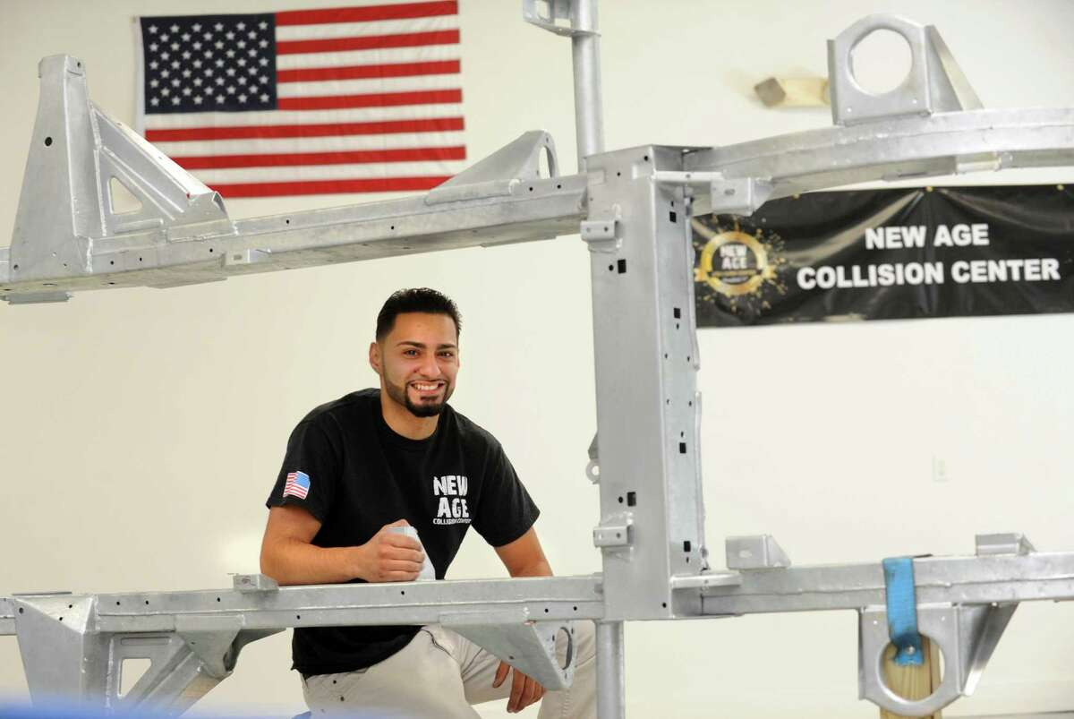 Ramon Soto-Rodriguez poses near a car frame at his recently opened a state of the art auto body shop, New Age Collision, on Federal St. in Brookfield, Conn. on Tuesday, Aug. 19, 2014. Soto-Rodriguez is excited about the redevelopment efforts near the Four Corners area of town.