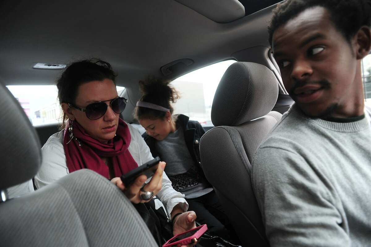 Anna Magelssen attempts to give directions to Lyft driver Jibril Jaha by using a communications application created by him as her daughter Bibiana Re-azco-Magelssen puts on her seatbelt on August 18, 2014 in San Francisco, CA. Jaha, who is deaf, has created an application called