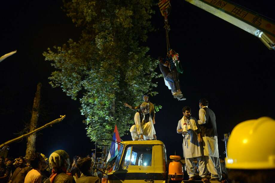 Supporters of Canada-based preacher Tahir-ul-Qadri climb on a crane to remove containers to march towards the parliament during an anti-government march in Islamabad on August 19, 2014. Pakistan on August 19 sent troops to boost security in Islamabad's government district, as opposition politician Imran Khan and a populist cleric led protesters marching on parliament in a high-stakes bid to depose the prime minister. Khan, the former cricket star who leads the Pakistan Tehreek-e-Insaaf (PTI) party, and preacher Tahir-ul-Qadri say last year's general election was rigged and have demanded Prime Minister Nawaz Sharif resign. AFP PHOTO / FAROOQ NAEEMFAROOQ NAEEM/AFP/Getty Images Photo: Farooq Naeem, AFP/Getty Images