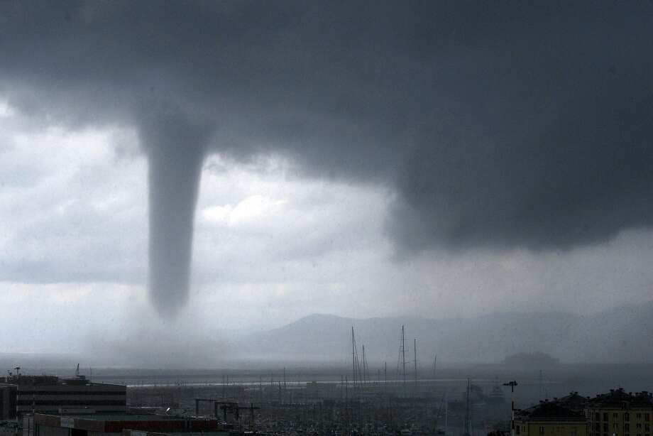 A tornado is seen approaching the costal city of Genoa, in Northern Italy, Tuesday, Aug 19, 2014. At right, in background, the profile of the Costa Concordia cruise liner wreck which was towed to Genoa for scrapping. Tornadoes and thunderstorms hit Genoa and the Liguria region coast Tuesday, causing damages to seaside cabins and floods but no victims. (AP Photo/Tano Pecoraro) Photo: Tano Pecoraro, Associated Press