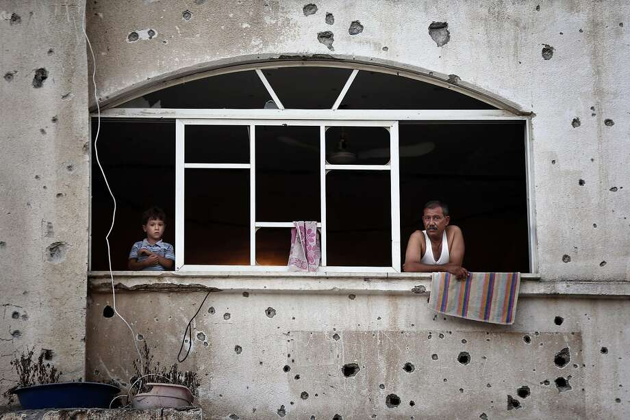 TOPSHOTS Palestinians look out of a window frame in their destroyed neighbourhood in the northern Gaza Strip city of Beit Hanun, on August 18, 2014. Prime Minister Benjamin Netanyahu warned that Israel will hit back hard if Palestinian rocket attacks from Gaza resume, speaking just hours before the midnight expiry of a five-day ceasefire. AFP PHOTO / THOMAS COEXTHOMAS COEX/AFP/Getty Images Photo: Thomas Coex, AFP/Getty Images