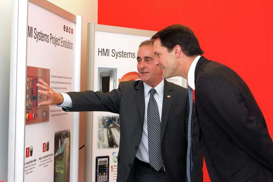 EAO Corp. President and CEO Lance Scott (left) shows Congressman Jim Himes the evolution of how his company's products end up in everyday devices during a tour of the Swiss company's new North American headquarters in Shelton, Conn. Photo: Contributed Photo / Connecticut Post Contributed
