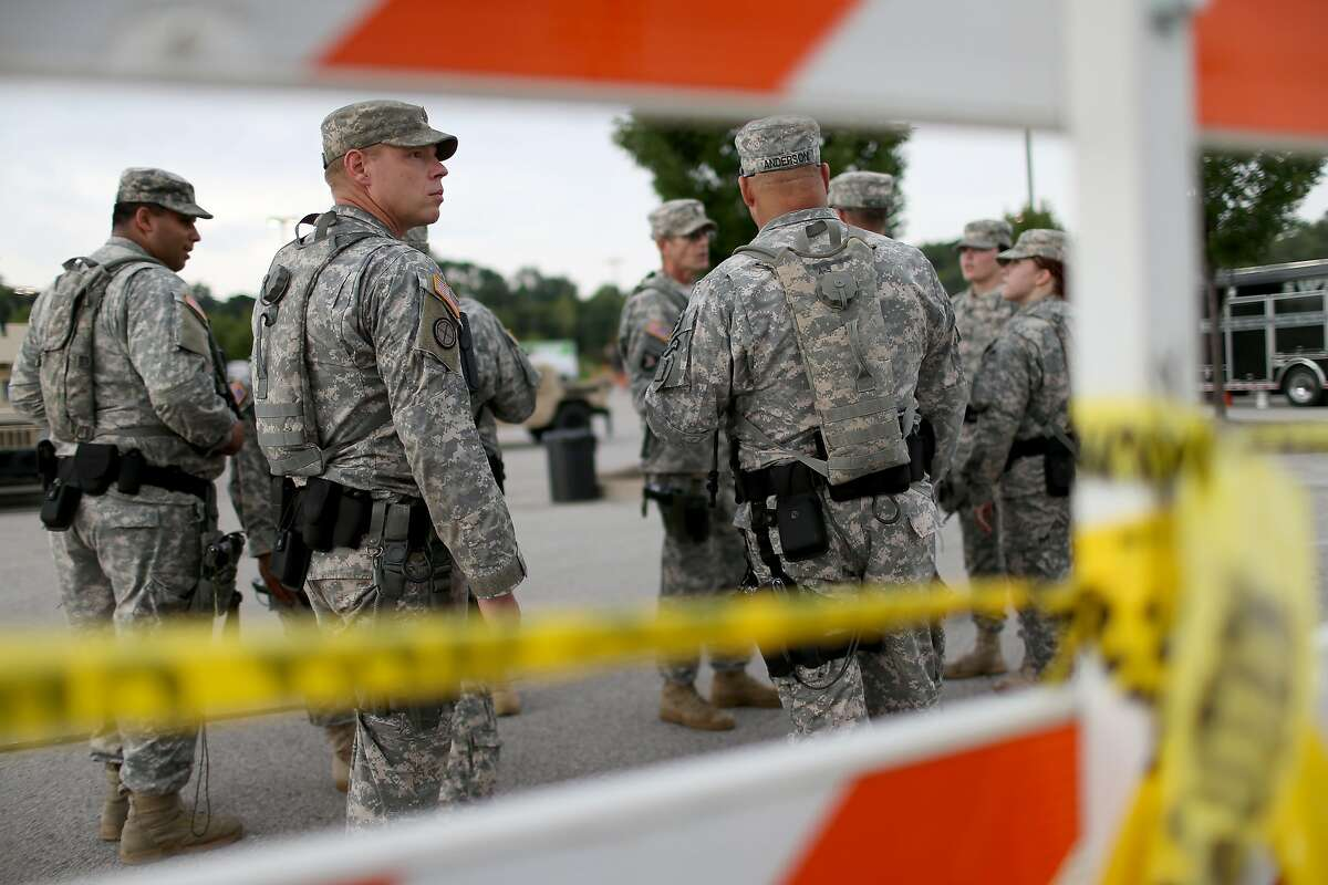 FERGUSON, MO - AUGUST 19: Missouri National Guard troops are deployed to provide protection for a police command center on August 19, 2014 in Ferguson, Missouri. Violent outbreaks have taken place in Ferguson since the shooting death of unarmed teenager Michael Brown by a Ferguson police officer on August 9. (Photo by Joe Raedle/Getty Images)