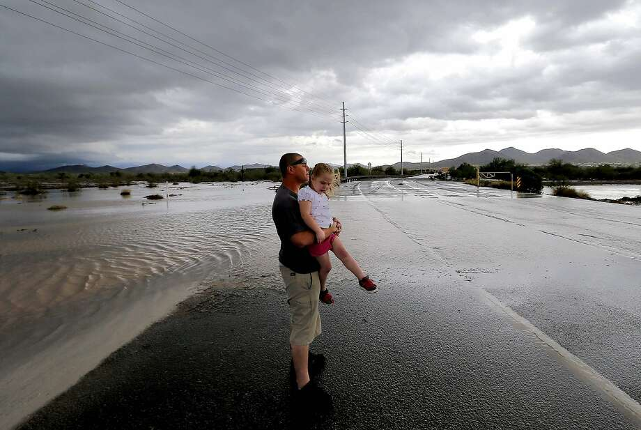 Josh Groves and daughter Abagayle, 3, wait to cross the road in northwestern Phoenix as flash flood waters overrun Skunk Creek through the Sonoran Desert. A portion of Interstate 17 was closed. Photo: Matt York, Associated Press