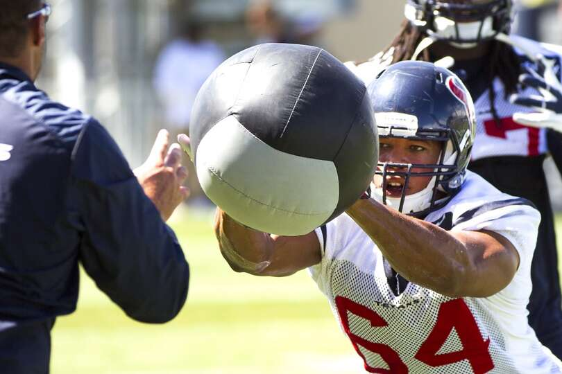 Texans linebacker Chris McAllister (64) knocks a ball back to linebackers coach Mike Vrabel.