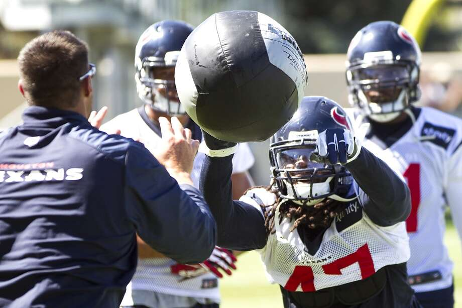 Texans outside linebacker Quentin Groves (47) knocks a ball back to linebackers coach Mike Vrabel. Photo: Brett Coomer, Houston Chronicle