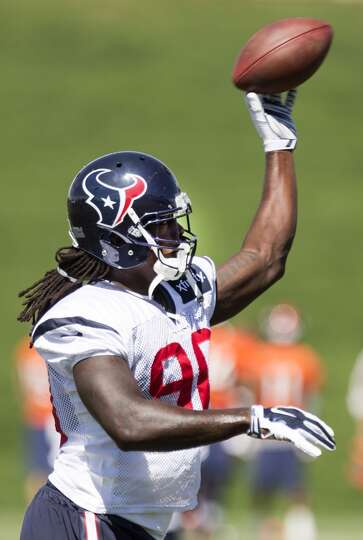 Texans linebacker Jadeveon Clowney (90) tosses a football back to a coach as he runs a drill.