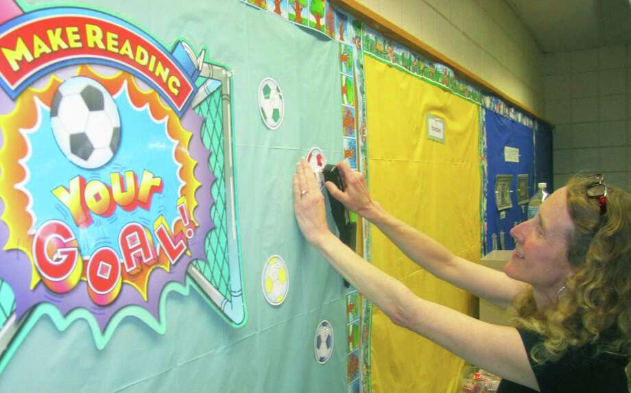 "Darcey Markelon, a special education teacher at Northville School in New Milford, arranges her ""Make Reading Your Goal"" bulletin board in preparation for the arrival of students on Aug. 25, 2014. Photo: Norm Cummings / The News-Times"
