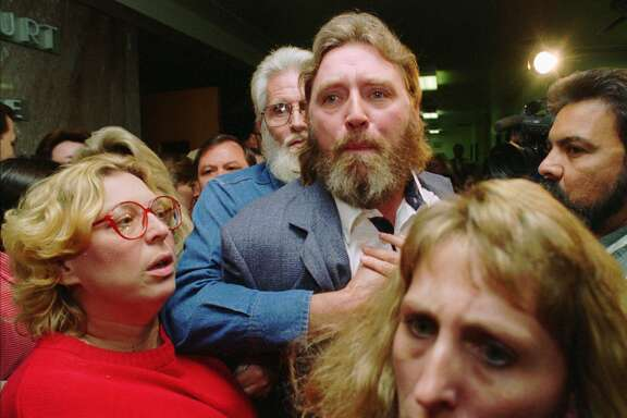 Randy Ertman is restrained Tuesday, Oct. 11, 1994, in Houston outside the courtroom where he addressed three of the five gang members convicted of killing his daughter and her friend. All five gang members were sentenced to death for the July 1993 slayings of his 14-year-old daughter, Jennifer, and Elizabeth Pena, 16.  (AP Photo/David J. Phillip)