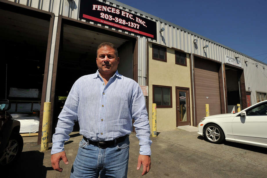 Dave Massi, owner of Fences Etc. Inc, poses for a photograph in front of his business in Stamford, Conn., on Tuesday, Aug. 19, 2014. Massi recently moved his business from Greenwich to Stamford to take advantage of the tax credits from the Enterprise Zone, which gives businesses a five-year, 80 percent local property tax abatement. Because of the abatement, Massi says, he was able to reinvest in his business, increasing the size of his shop. Photo: Jason Rearick / Stamford Advocate