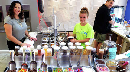 Beth Tepper, left, her husband Jacob, right, and employee Ashley Mauro, 18, pose inside Berry Chill, a new frozen yogurt business in Shelton on Saturday, August 19, 2014. The family operated business offers a variety of frozen yogurts, such as non fat, low fat, sugar free, dairy freeand even gluten free.
