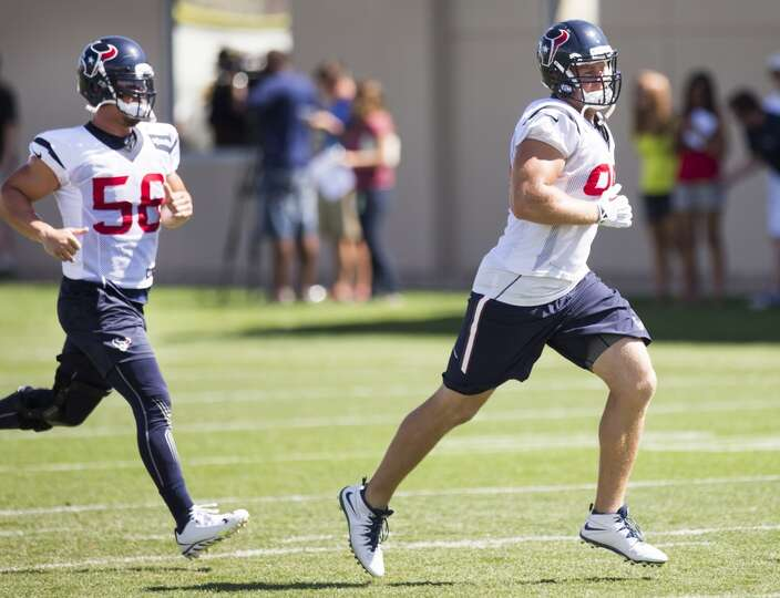Texans inside linebacker Brian Cushing (56) and defensive end J.J. Watt (99) jog across the practice