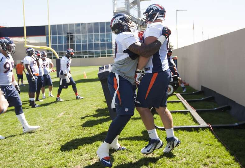 Broncos defensive tackle Kevin Vickerson (99) hits defensive end Will Pericak (69).