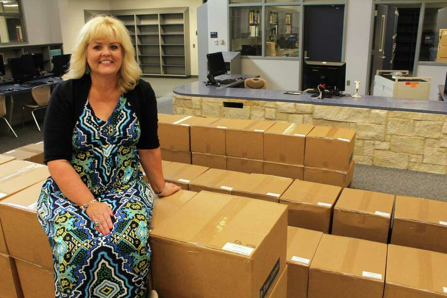 Keiko Davidson Elementary Principal Lisa Leethem sits atop boxes of books inside the school library that will be going into each classroom. Keiko Davidson Elementary Principal Lisa Leethem sits atop boxes of books inside the school library that will be going into each classroom. Photo: Suzanne Rehak, Freelance Photographer
