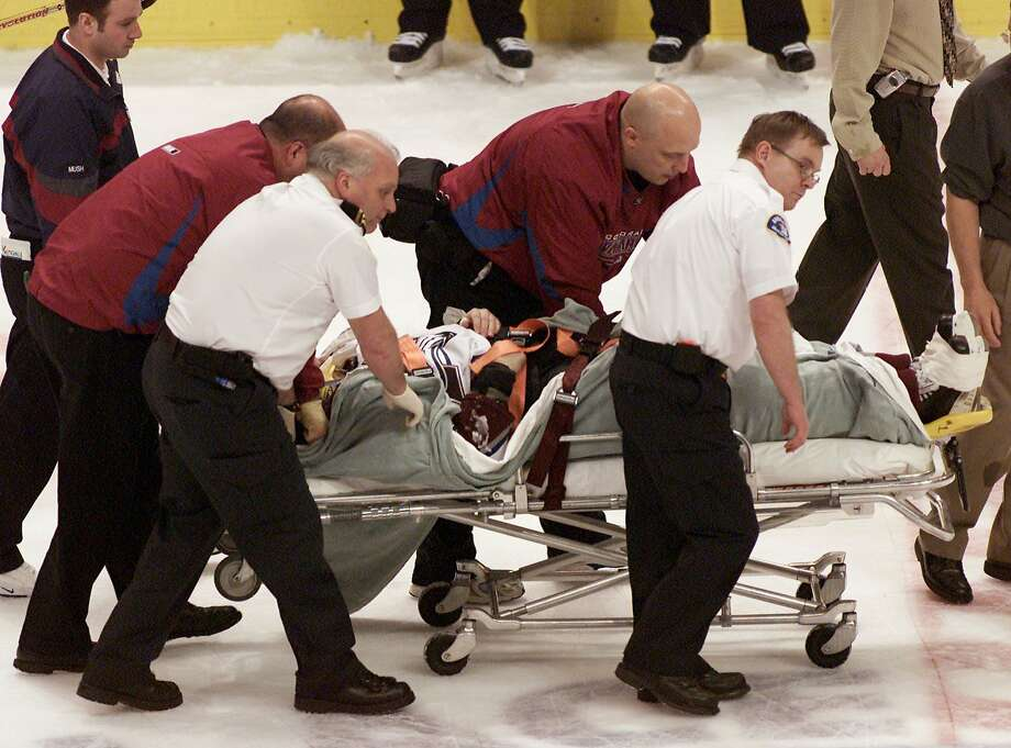 Avalanche forward Steve Moore is carted off the ice after he was hit by the Canucks' Todd Bertuzzi during the third period of a game on March 8, 2004, in Vancouver, British Columbia. Photo: Chuck Stoody, Associated Press