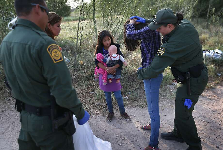 Border Patrol agents search a Salvadoran girl as her sister watches after the two were caught crossing the border illegally at Mission, Texas, in July. Photo: John Moore, Getty Images