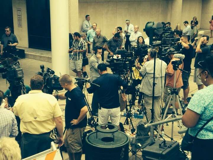 Media wait for Gov. Rick Perry to be booked at the Travis County Courthouse.