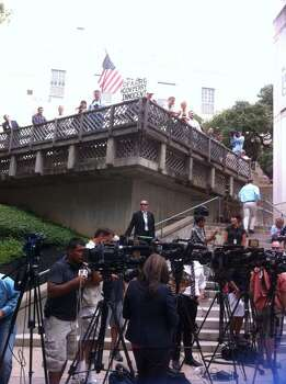 Media and Perry backers (w/flag) await his booking. Photo: Peggy Fikac/San Antonio Express-News