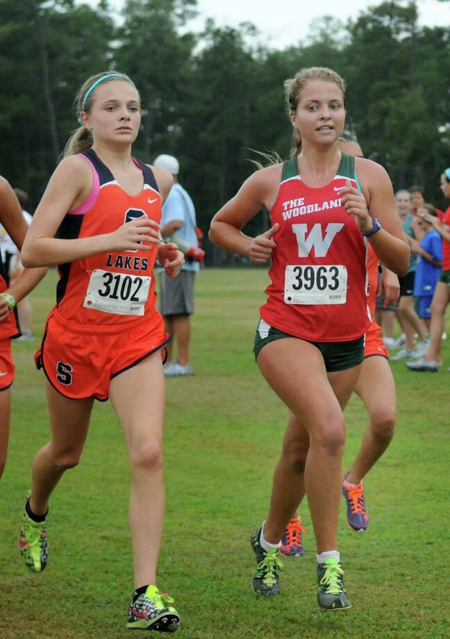 The Woodlands' Anna Lyons, right, pulls away from Seven Lakes' Kacie Corbin during the Girls Gold Division five-kilometer race at the Region 3 Preview Cross Country Meet at Atascocita High School. Photo: Jerry Baker, Freelance