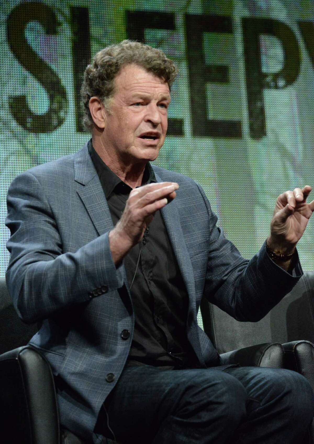 John Noble speaks on stage during the
