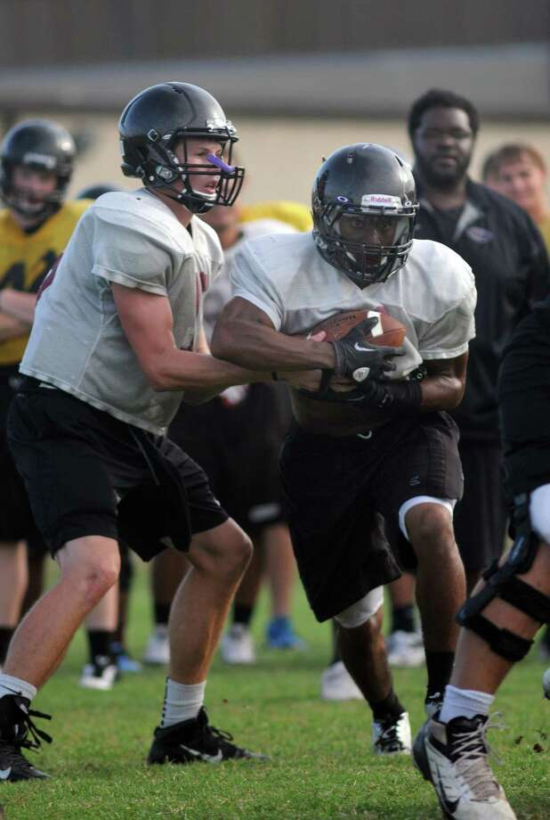 Pearland senior running back JaColbie Butler, right, takes a handoff from senior quarterback Jake Blumrick during an Oiler practice this month. Photo: Jerry Baker, Freelance