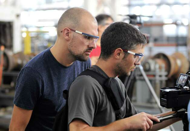 "Michael Cammidge, director of a film crew from Yap Films, a Toronto based independent film company, works with Natalino ""Vito"" Latanzio, B camera operator, right, while coordinating a documentary on weapons manufacturing Tuesday, Aug. 19, 2014, at the Watervliet Arsenal in Watervliet, N.Y.   The documentary will appear on Discovery International and the History Channel Canada in 2015. (Will Waldron/Times Union) Photo: WW"
