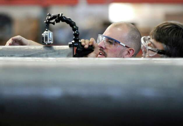 Michael Cammidge, left, director of a film crew from Yap Films, a Toronto based independent film company, works with Aaron Szimanski, right, director of photography, right, while coordinating a documentary on weapons manufacturing Tuesday, Aug. 19, 2014, at the Watervliet Arsenal in Watervliet, N.Y.   The documentary will appear on Discovery International and the History Channel Canada in 2015. (Will Waldron/Times Union) Photo: WW