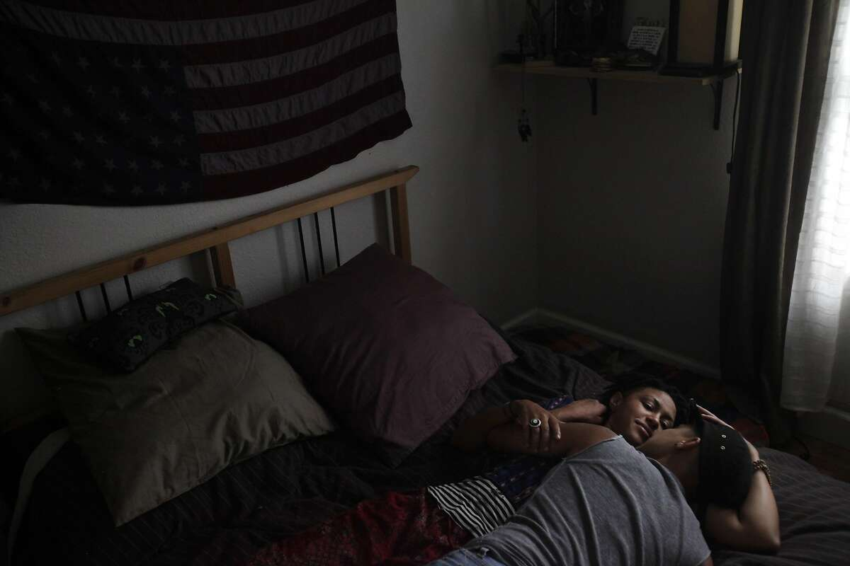 Partners Barbara Jefferson, 29, left, and Sonj Basha, 26, lay in their bed together after dinner August 7, 2014 at their home in Oakland, Calif. Basha, who identifies as gender queer, was part of the Gender Identity and Expression Committee that developed a new policy for Mills College on the inclusion of transgender and gender fluid students at the school. Jefferson identifies as gender neutral.