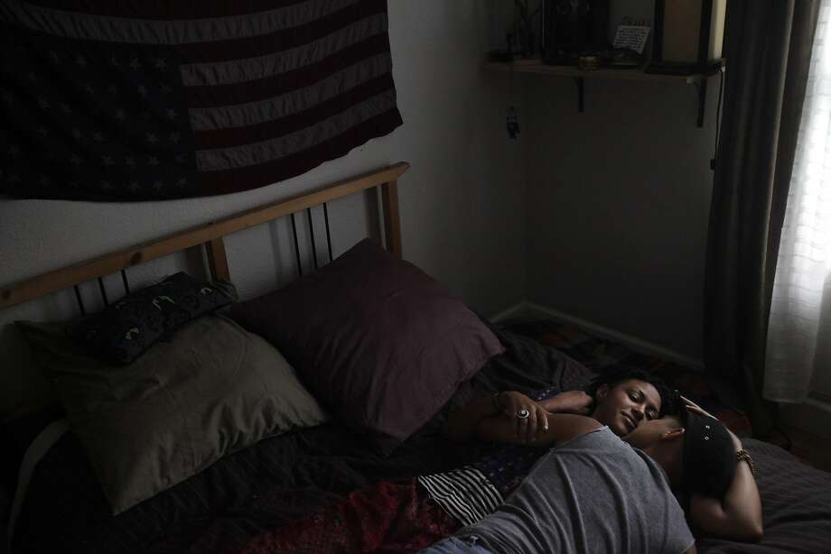 Sonj Basha (right), a student who helped shape Mills College's gender policy, lies in bed  with partner Barbara Jefferson, who also is gender neutral, at their home in Oakland. Photo: Leah Millis, The Chronicle