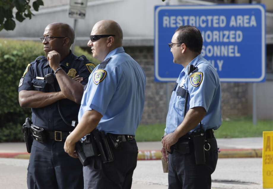 Houston Police officers shown gathered at 61 Riesner where Jodi Silva, a spokesperson for the Houston Police Department, has confirmed that a Houston police officer has died from a gunshot wound on the second floor of the parking garage Tuesday, Aug. 19, 2014.