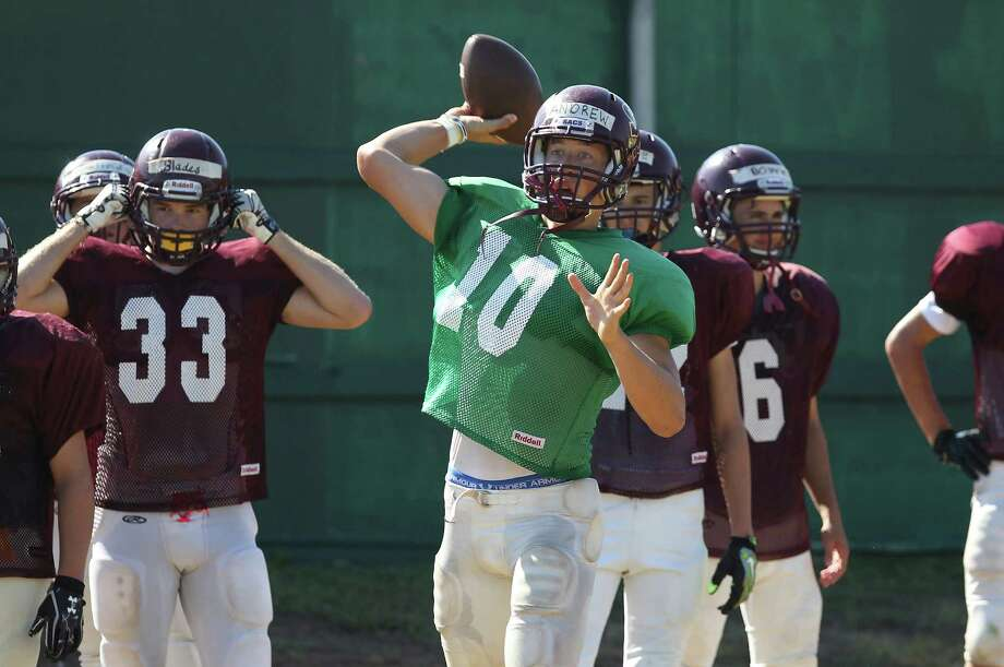 San Antonio Christian quarterback Andrew Hawkins (center) throws a pass during practice on Thursday, Aug. 14, 2014. Hawkins is a senior who threw for 2,279 yards and 28 TDs in 2013 for the Lions in TAPPS Division II last year. The Lions will be playing in TAPPS Division I this season. Photo: Kin Man Hui, San Antonio Express-News / ©2014 San Antonio Express-News