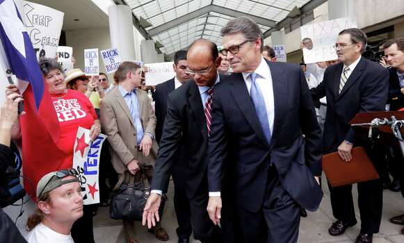 Texas Gov. Rick Perry, front right, is escorted away from the Blackwell Thurman Criminal Justice Center, Tuesday, Aug. 19, 2014, in Austin, Texas. Perry has been booked on two felony counts of abuse of power for carrying out a threat to veto funding to state public corruption prosecutors. (AP Photo/Eric Gay) Photo: Eric Gay, Associated Press / AP