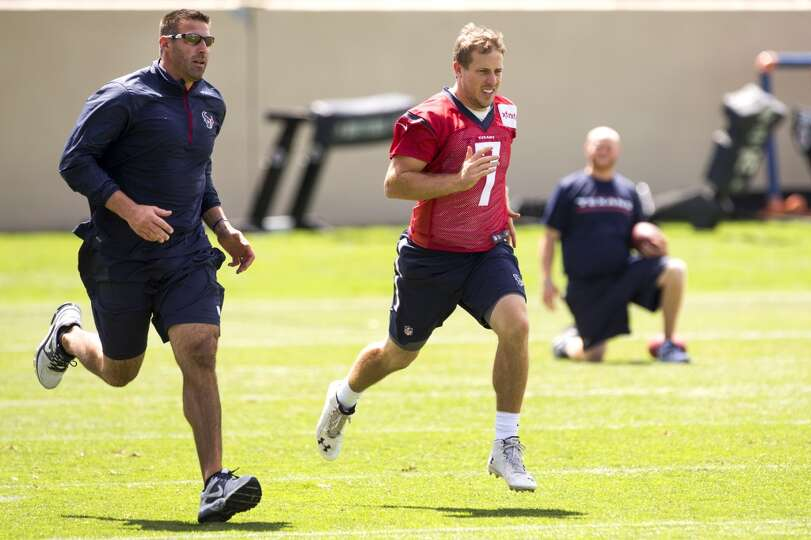 Texans linebackers coach Mike Vrabel, left, runs with quarterback Case Keenum (7) following a joint