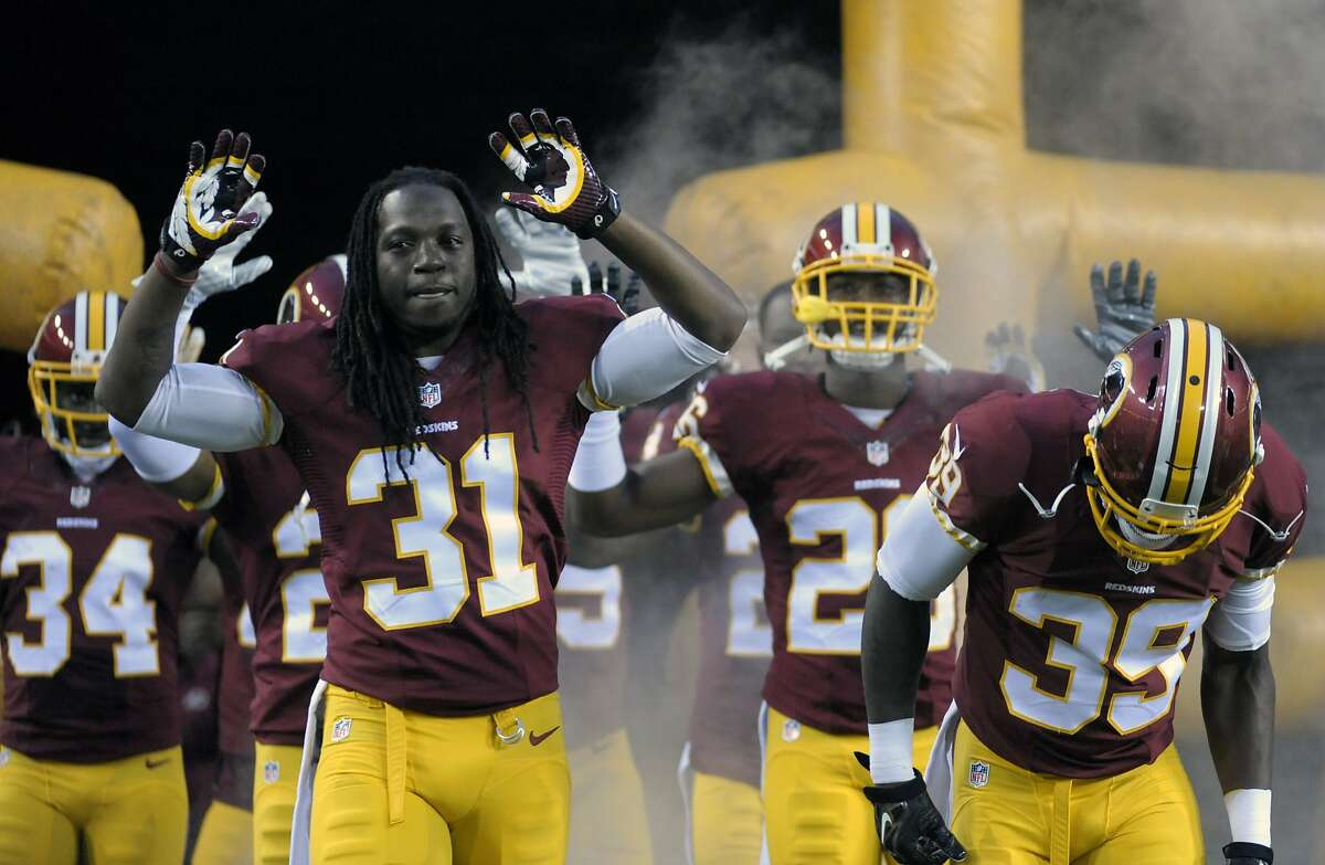 In this Aug. 18, 2014, photo, Washington Redskins strong safety Brandon Meriweather (31) along with other teammates enter FedEx Field with their arms raised before an NFL game against the Cleveland Browns in Landover, Md. The