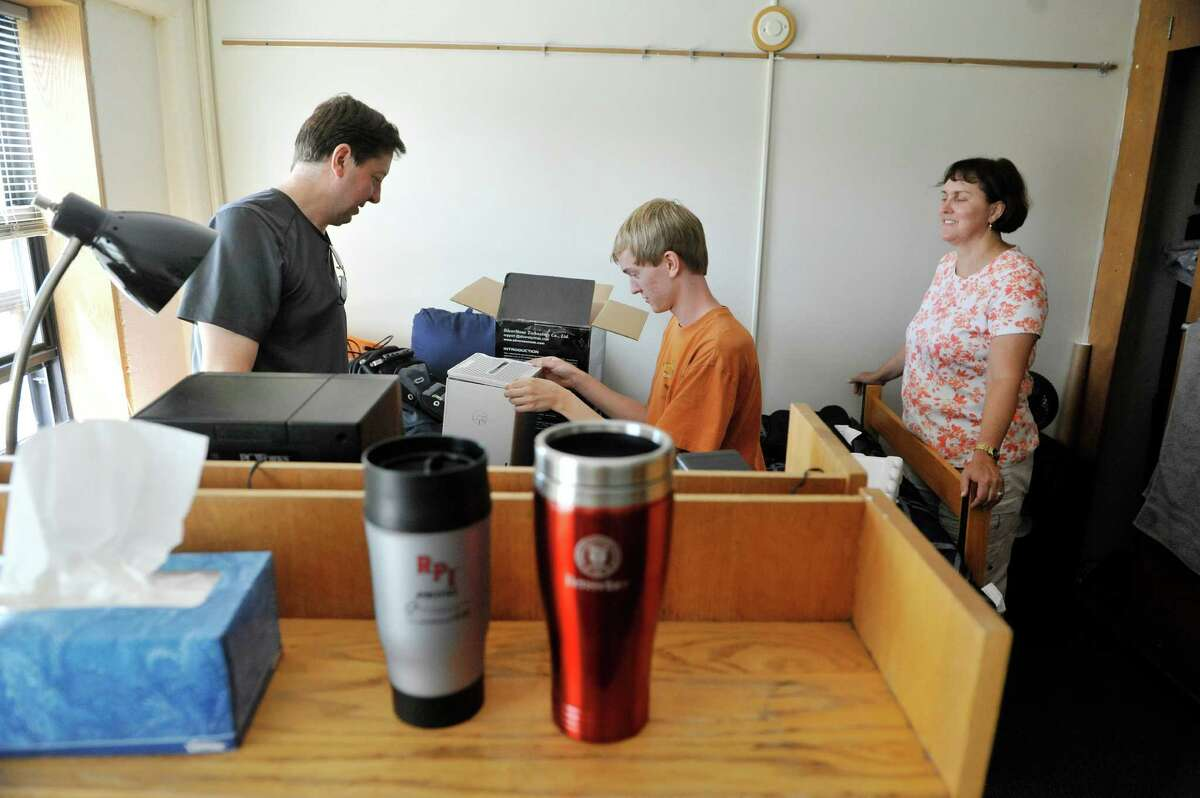Jon Durkee, left, and his wife, Sue Durkee, right, from Lynnfield, Mass., help their son William set up his dorm room during freshman move-in day at RPI, on Tuesday, Aug. 19, 2014, in Troy, N.Y. Durkee will be studying engineering. (Paul Buckowski / Times Union)