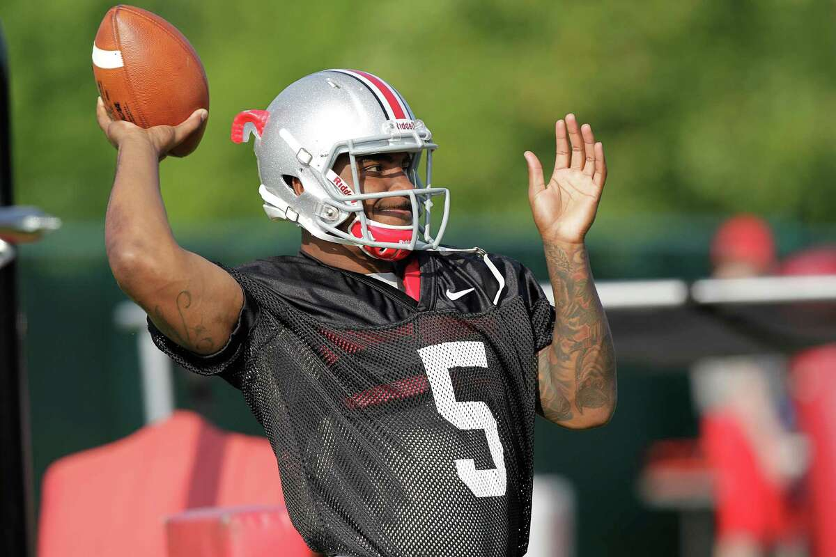 FILE - In this Aug. 9, 2014, file photo, Ohio State quarterback Braxton Miller warms up during an NCAA college football practice, in Columbus, Ohio. Miller, among the top contenders for the Heisman Trophy, reportedly reinjured his throwing shoulder during practice. The report about the two-time Big Ten offensive player of the year comes with just more than two weeks before the No. 5 Buckeyes open the season. (AP Photo/Jay LaPrete, File) ORG XMIT: NY155