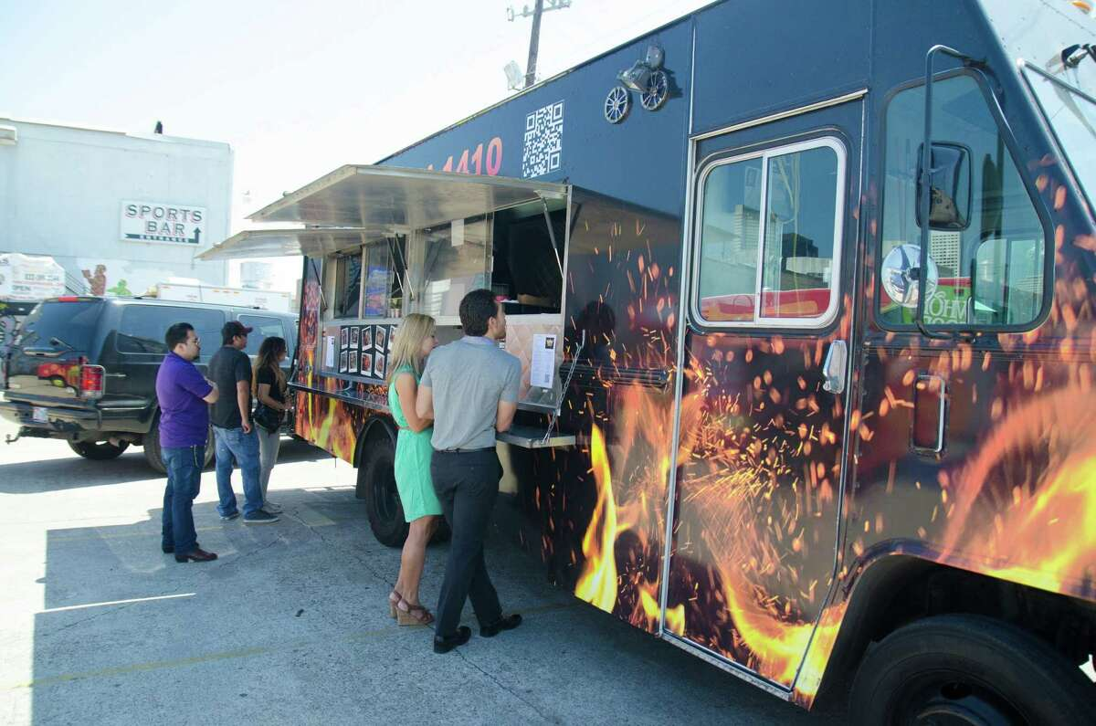 Customers line up during lunch at Reign Food Truck at Houston Food Park near downtown.