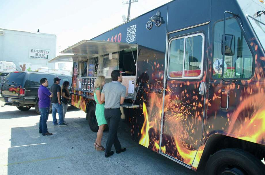Customers line up during lunch at Reign Food Truck at Houston Food Park near downtown. Photo: Jamaal Ellis / ©2014 Houston Chronicle