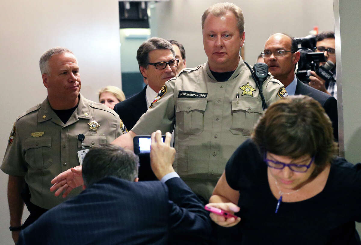 Texas Governor Rick Perry goes through the process of being booked for felony charges at the Travis County Courthouse in Austin on August 20, 2014.