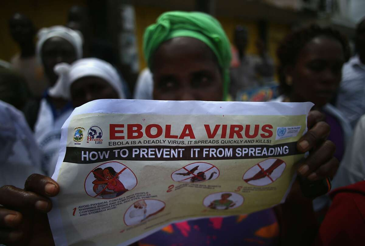 Public health advocates stage street theater to attract people to attend an Ebola awareness and prevention event on August 18, 2014 in Monrovia, Liberia.