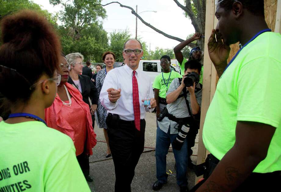 (center) The U.S. Secretary of Labor Thomas E. Perez greets YouthBuild students (l-r) Tyjeniea Jackson and Trevion Coleman, Tuesday August 19, 2014 at YouthBuild in Houston, TX. Perez  toured the Houston YouthBuild facility and watched as students demonstrated their skills installing a lighting fixtures. (Billy Smith II / Houston Chronicle) Photo: Billy Smith II, Staff / © 2014 Houston Chronicle