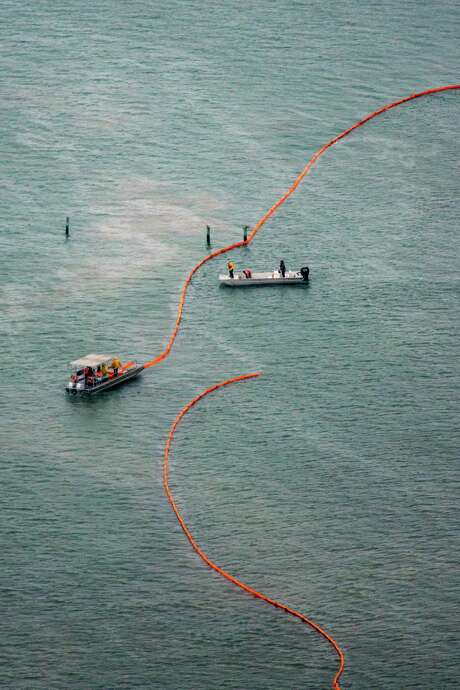 Crews place protective boom near Port Bolivar after an oil spill in March.  Photo: Smiley N. Pool, Staff / © 2014  Houston Chronicle