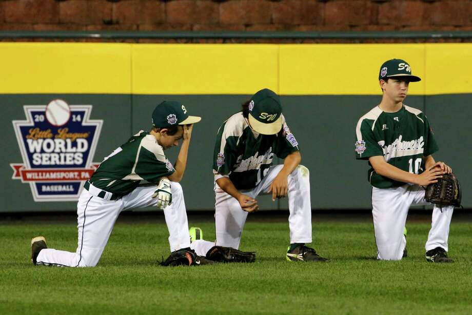 Pearland outfielders Presley Smith, left, Clayton Broeder, center, and Cole Smajstrla kneel in the outfield during a pitching change during the fourth inning of an elimination baseball game against Chicago at the Little League World Series tournament in South Williamsport, Pa., Tuesday, Aug. 19, 2014. (AP Photo/Gene J. Puskar) Photo: Gene J. Puskar, Associated Press / AP