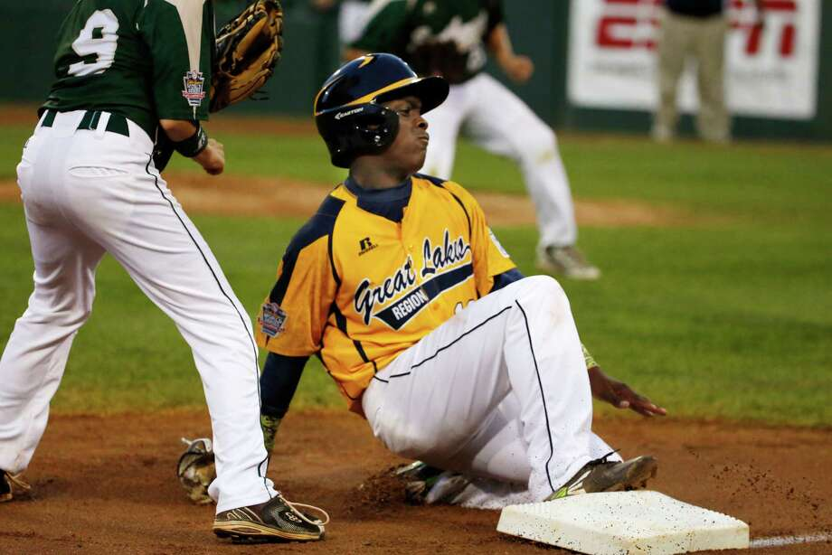 Chicago's Marquis Jackson, right, slides safely into third as the ball gets past Pearland third baseman Michael Groover (9), allowing Jackson to score, on a single by Chicago's Darion Radcliff during the first inning of an elimination baseball game at the Little League World Series in South Williamsport, Pa., Tuesday, Aug. 19, 2014. (AP Photo/Gene J. Puskar) Photo: Gene J. Puskar, Associated Press / AP
