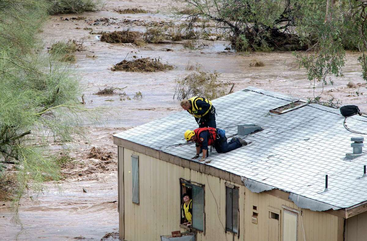 Firefighters talk with Tracey Tumlinson before she was rescued, Tuesday, Aug. 19, 2014, from her home flooded by the New River Wash, in New River, Arizona. (AP Photo/The Arizona Republic, Mark Henle) MARICOPA COUNTY OUT; MAGS OUT; NO SALES ORG XMIT: AZPHP301