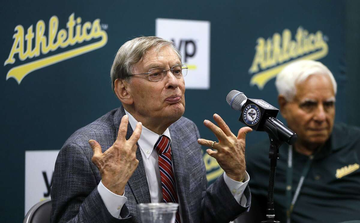 Baseball commissioner Bud Selig, left, gestures during a news conference prior to a baseball game between the New York Mets and the Oakland Athletics on Tuesday, Aug. 19, 2014, in Oakland, Calif. At right is Oakland Athletics co-owner Lewis Wolff. (AP Photo/Ben Margot)