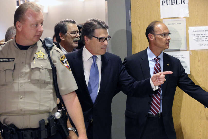 Gov. Rick Perry wore his new glasses to the courthouse complex but took them off for his mug shot.